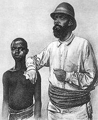 Un portrait de l'explorateur allemand Richard Kund posant la main sur un jeune camerounais © Wikipédia